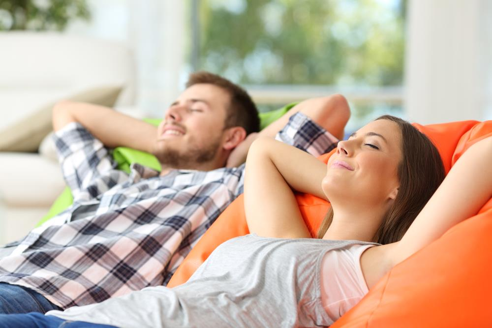 Couple or roommates relaxing lying on comfortable upload article